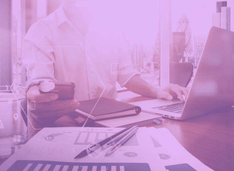 Imagem ilustrativa, na cor lilás. Com um homem sentado ao computador segurando uma calculadora, para respresentar alguém que está trabalhando em um processo de compras.